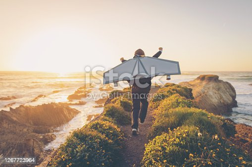A young boy dressed in business suit and tie wears a homemade jetpack and flying goggles raises his arms in the afternoon sun while running to take off into the air on an outcropping above the surf in California. This young entrepreneur is ready to take his new business to new heights.