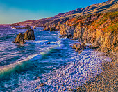 Seascape of Big Sur coastline at dusk with breaking waves fanning out on a rocky cove with two sea stacks on the left side, Big Sur California