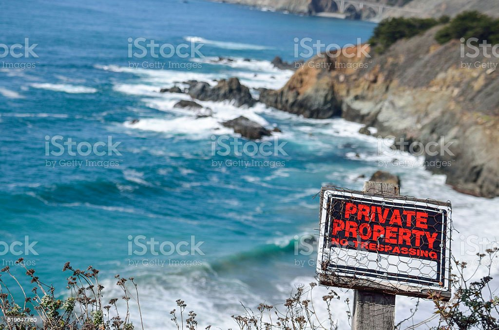 California coast with cliffs and private property sign stock photo