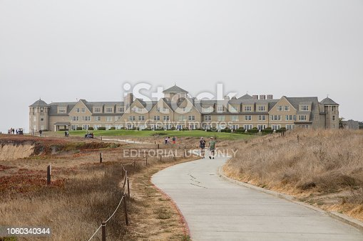 Half moon Bay, CA, USA - August 18, 2018:  Half moon Bay is about 45 minutes south of San Francisco. It's a small coastal town with an almost perfect Mediterranean climate. The ritz Calton hotel on the back ground. Incidental people are walking on the road.