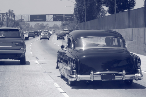 A restored classic car cruising the freeways of Los Angeles.