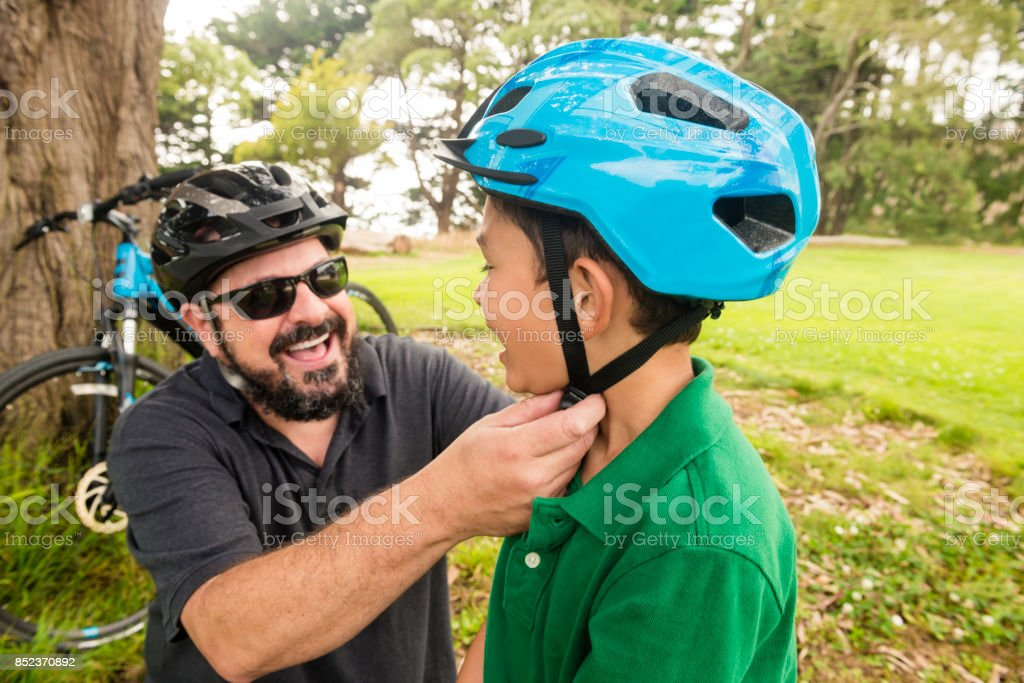 California Father Puts Helmet on Son Before Riding Bikes Outdoors stock photo