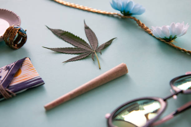 California Festival Essentials on Light Blue with a Joint, Marijuana Leaf, Flower Crown, Turquoise, Sunglasses - Angled stock photo