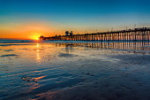The pier in Oceanside, California located in northern San Diego County as the sun sets behind it.