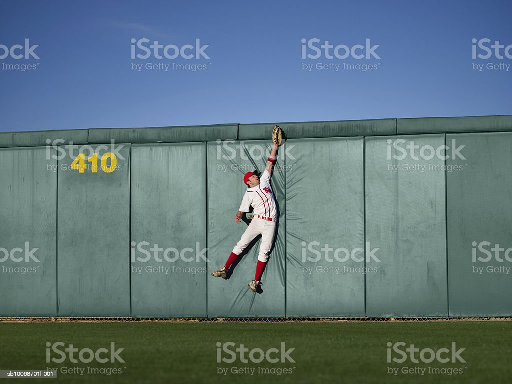 USA, California, San Bernardino, baseball player making leaping catch at wall 免版稅 stock photo