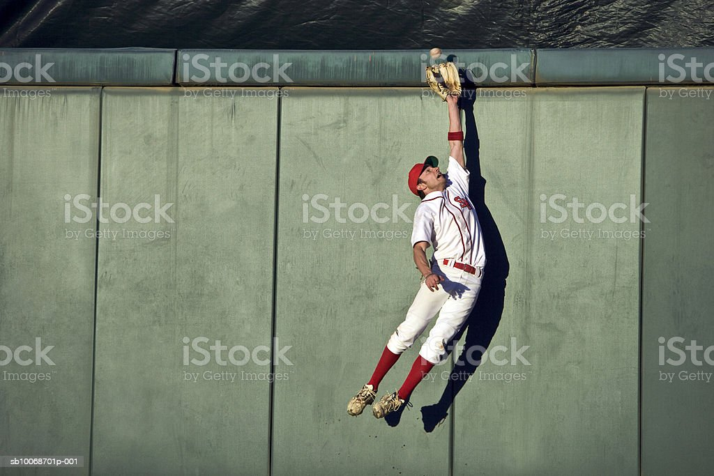 USA, California, San Bernardino, baseball player making leaping catch at wall royalty-free stock photo