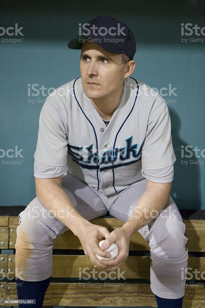 USA, California, San Bernardino, baseball player sitting in dugout royalty free stockfoto