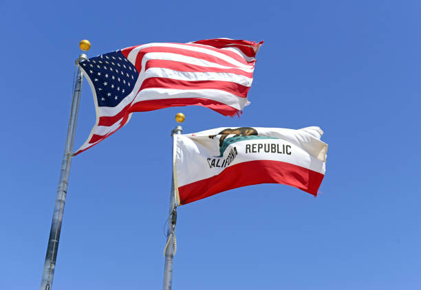 Bandera del estado de California y la bandera americana con fondo de cielo azul, ondeando en el viento - foto de stock