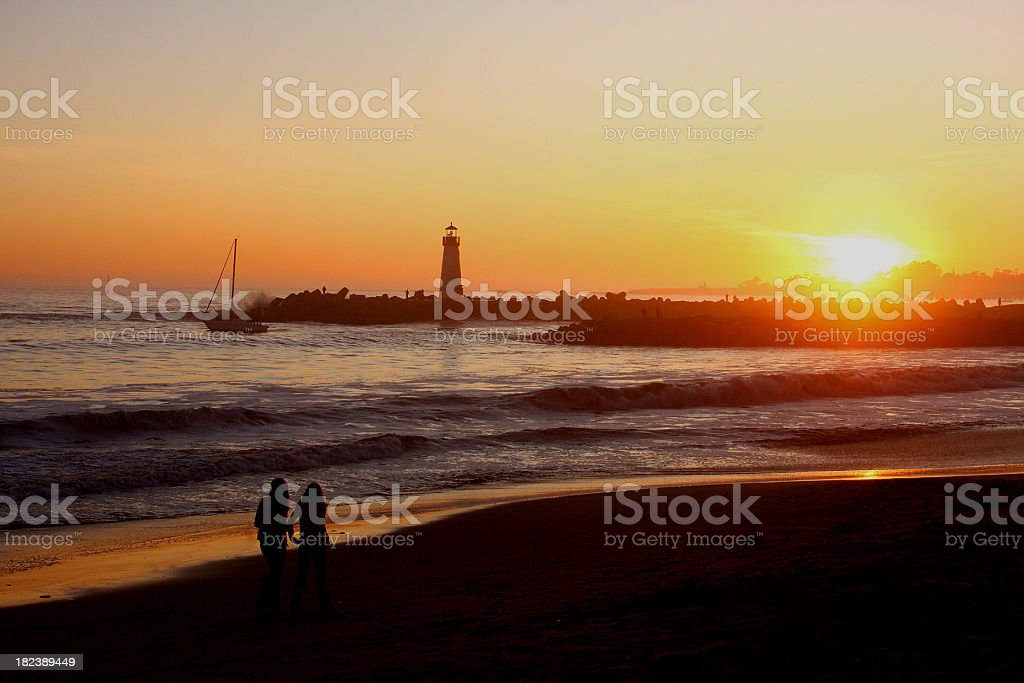 California sunset, lighthouse, sailboat and two girls royalty-free stock photo