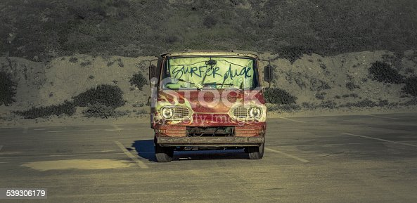 An old van parked in a Southern California Beach parking lot. Van owned, operated and lived in by the California Surfer Dude. The van is a red, 60's model with painted flames. In the windshield hangs a cloth with