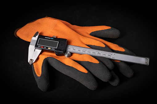 Caliper for taking measurements and protective gloves. Measuring and protective tools for builders. Dark background.