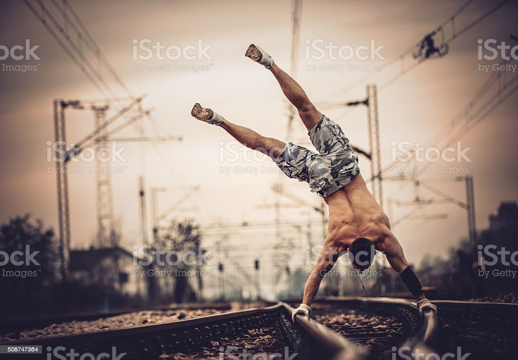Calisthenics on railroad tracks. stock photo