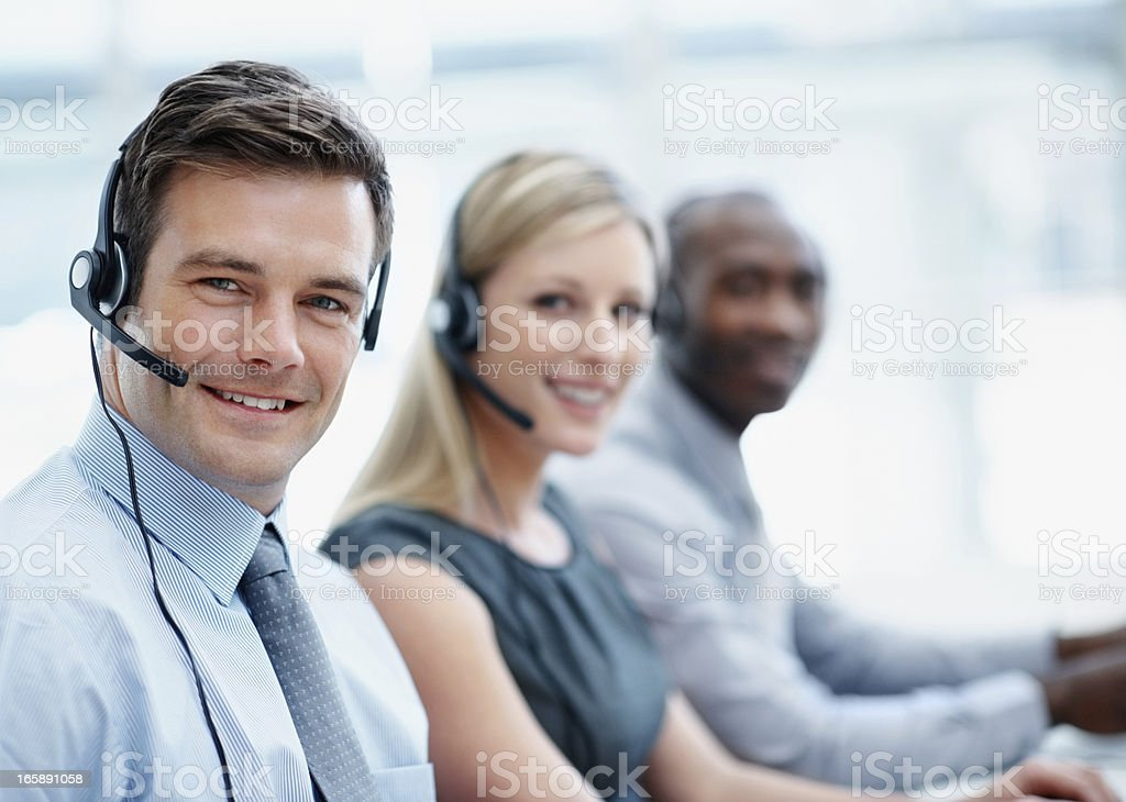 Call Center Businesspeople Smiling With Headsets Stock Photo