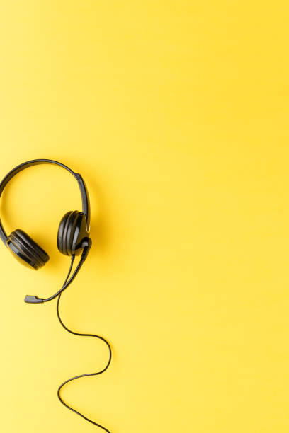 Call center concept. Helpdesk headset on yellow desktop with copyspace stock photo