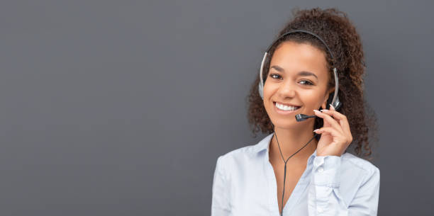 Call center employee isolated on a gray background. stock photo