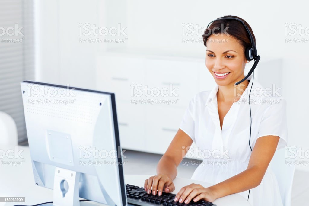 Smiling female call center worker typing on computer keyboard....