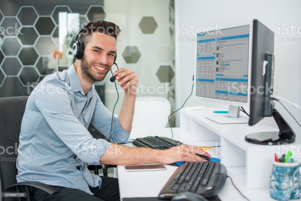 Call center male operator working on computer at office