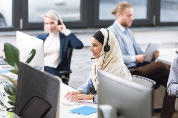call center operator in headset at workplace stock photo