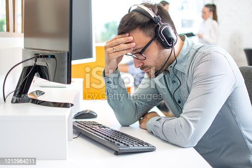 932342408istockphoto Call center operator man wearing headset suffering from headache at office 1212984211