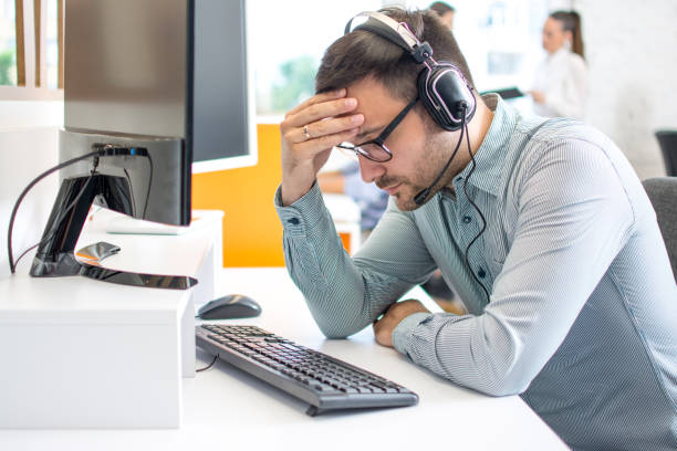 Call center operator man wearing headset suffering from headache at office stock photo