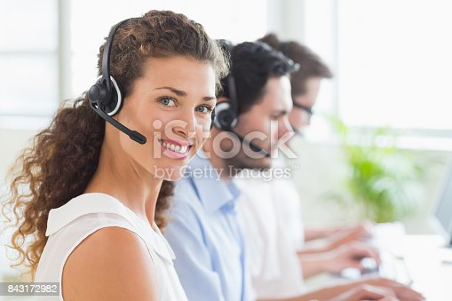 istock Call center operator wearing headset in office 843172982