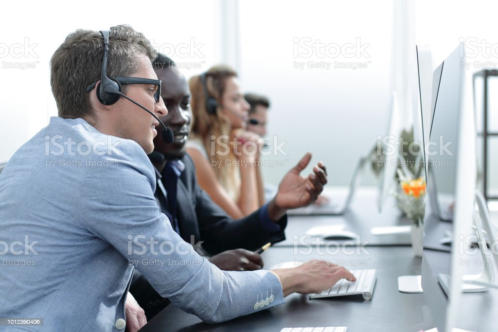 call center operators are talking, sitting at his Desk stock photo