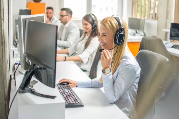 Call center operators.Young beautiful business woman with headset working on computer in office with colleagues in the background. stock photo