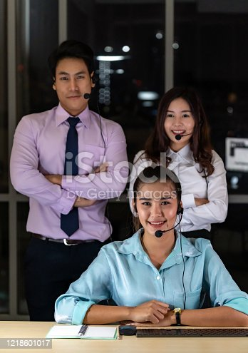 Late Night Environment, Potrait of friendly Call centre operator team with headsets in a call center customer service and technical support. Using for 24 Hr. Call center Concept.