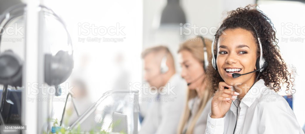 Call center worker accompanied by her team. stock photo