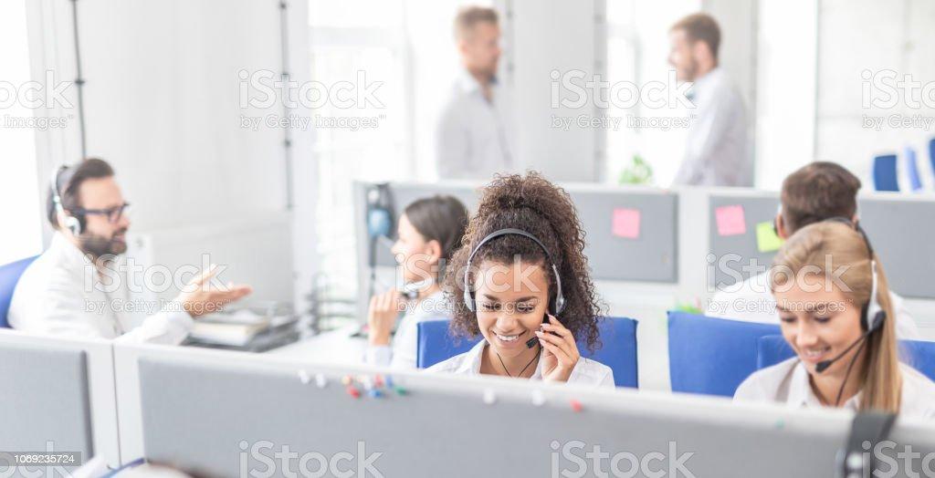 Callcenterarbeitskraft von ihrem Team begleitet. – Foto