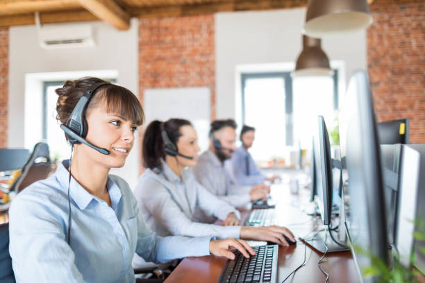 call center worker accompanied by her team. - call center stock photos and pictures