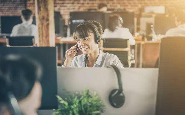 Call center worker accompanied by her team. Call center worker accompanied by her team. Smiling customer support operator at work. Young employee working with a headset. call centre photos stock pictures, royalty-free photos & images