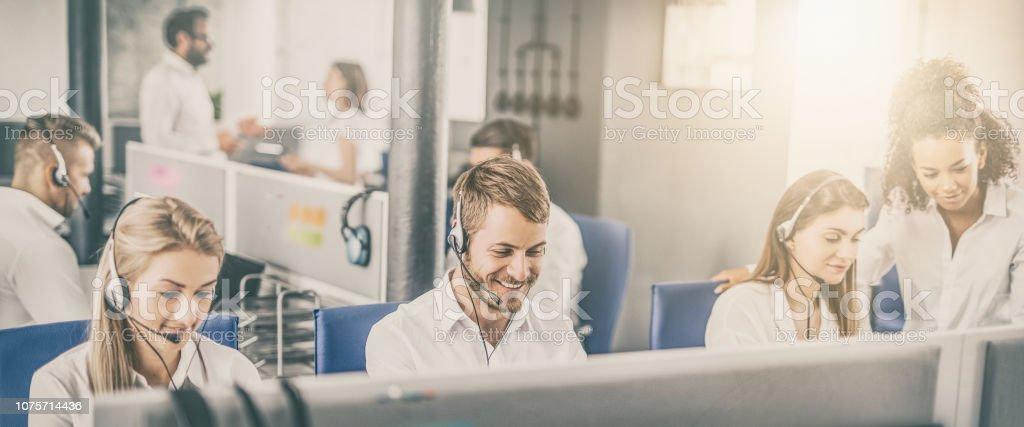 Callcenterarbeitskraft von seinem Team begleitet. – Foto