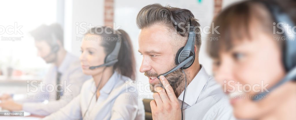 Call center worker accompanied by his team. stock photo