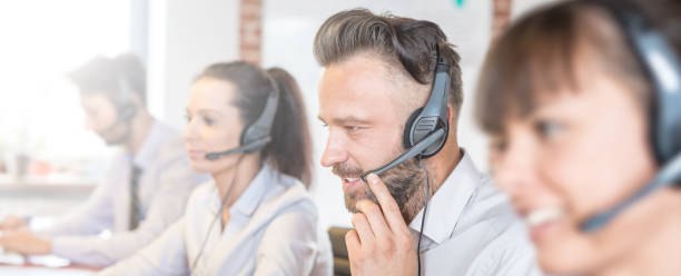 call center worker accompanied by his team. - call center stock photos and pictures