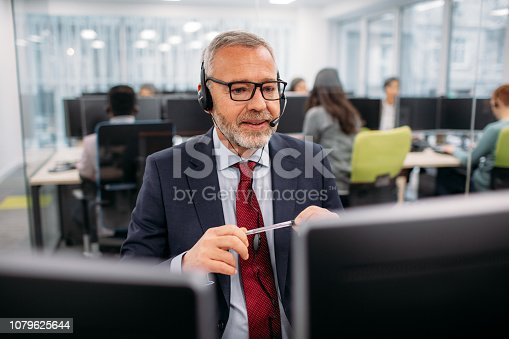 Call center workers sitting by the desk in their office and working. Selective focus on man with grey hair and eyeglasses.