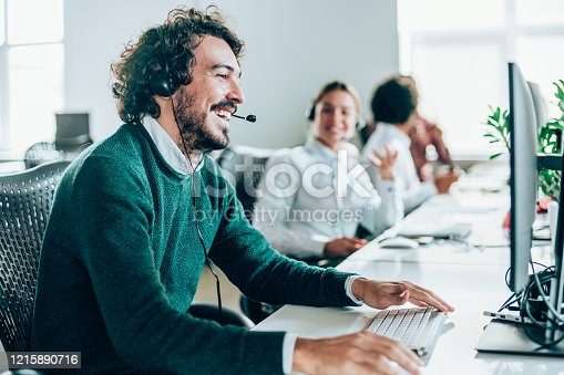 Smiling handsome young businessman working in call center. Shot of a cheerful young man working in a call center with his team. Confident male operator is working with colleagues. Call center operators sitting in a row at desks.