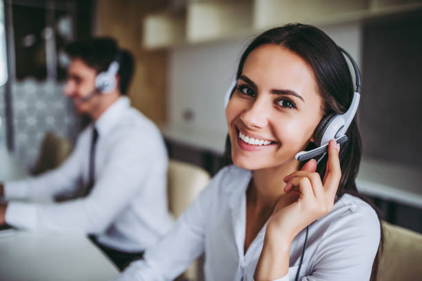 Call center workers. How can I help you? Beautiful call center workers in headphones are working at modern office. call centre photos stock pictures, royalty-free photos & images