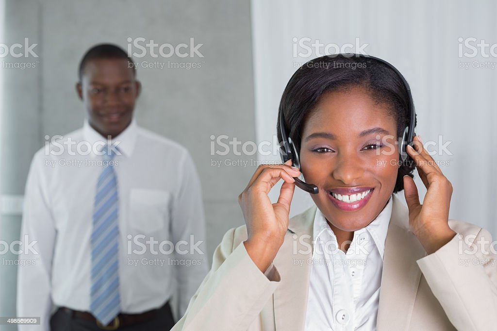 Call centre agent talking on the headset smiling at camera royalty-free stock photo