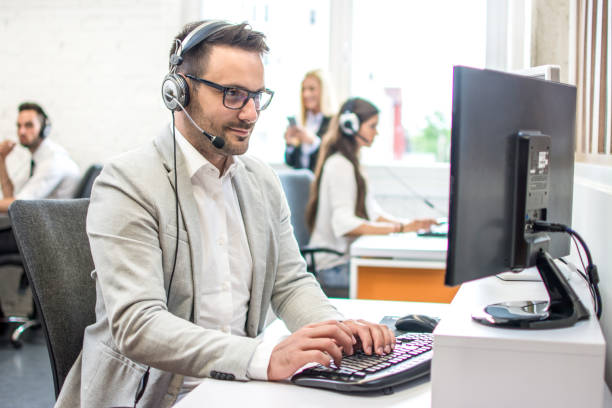 Call centre agent with headset working on computer in customer support helpdesk office stock photo