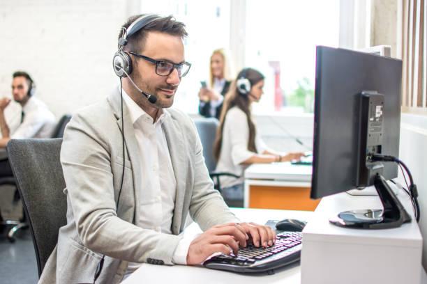 Callcenter-Agent mit Headset am Computer im Helpdesk-Büro des Kundensupports – Foto