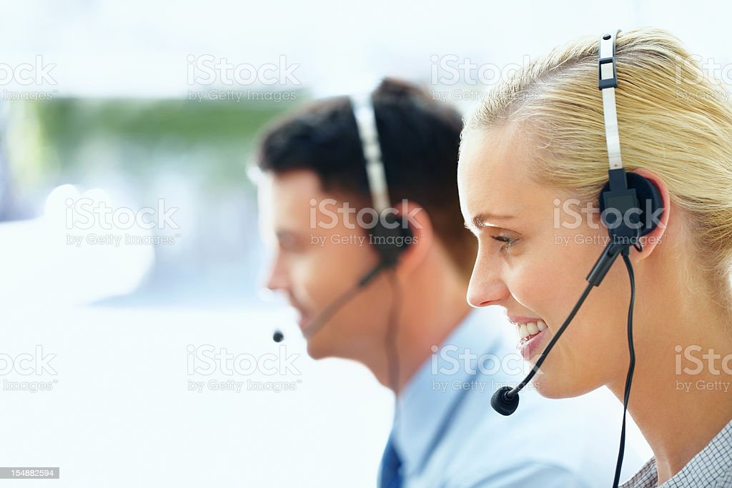 Call centre executive wearong headset with colleague in background royalty-free stock photo
