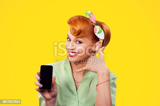istock Call me. Closeup red head young woman pretty smiling pinup girl green button shirt holding phone showing call me sign hands gesture looking at you camera, retro vintage 50's hairstyle. Body language 667652934