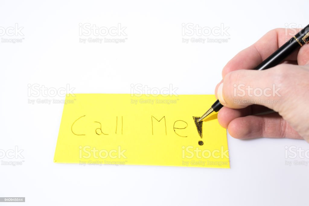 Call me handwrite with hand and pen on a yellow paper composition stock photo