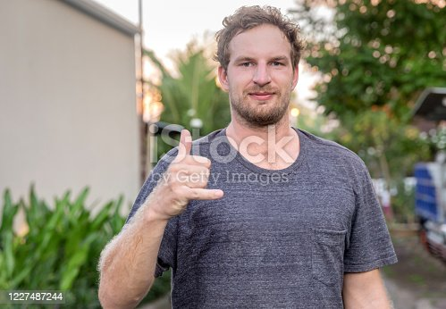 Close up portrait shot of male surfer giving 'Hang Loose' sign gesture to say goodbye and avoid physical contact amid Covid 19