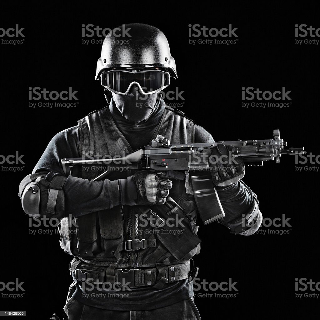 Modern military soldier holding a rifle. Studio shot on black...