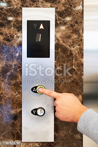 638591126 istock photo Call the elevator. A man calls a lift with his finger for a ride up, the digging is lit in green. Hand and panel closeup 1181523797