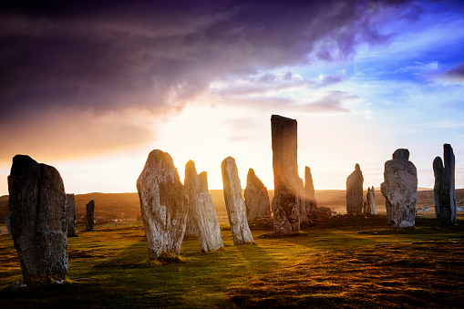 The ancient standing stones of Callanish (or Calanais) on Lewis in the Outer Hebrides of Scotland at sunrise on a stormy spring morning. Built about 5000 years ago, the deeply textured stones of Callanish are arranged in allignments of avenues and a central circle not unlike a celtic cross.