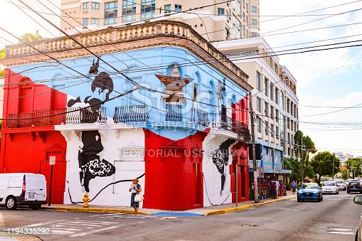 This photograph is of the street scene on Calle Loiza in the San Turce neighborhood of San Juan, Puerto Rico. A corner building is painted with the Puerto Rican flag. Cars and people can be seen along the street and sidewalk.ci