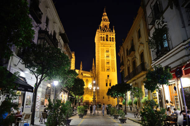 Calle Mateo Gagos with La Giralda de Sevilla in the background. Seville, Spain - June 21, 2018: Calle Mateo Gagos with La Giralda de Sevilla in the background. santa cruz seville stock pictures, royalty-free photos & images